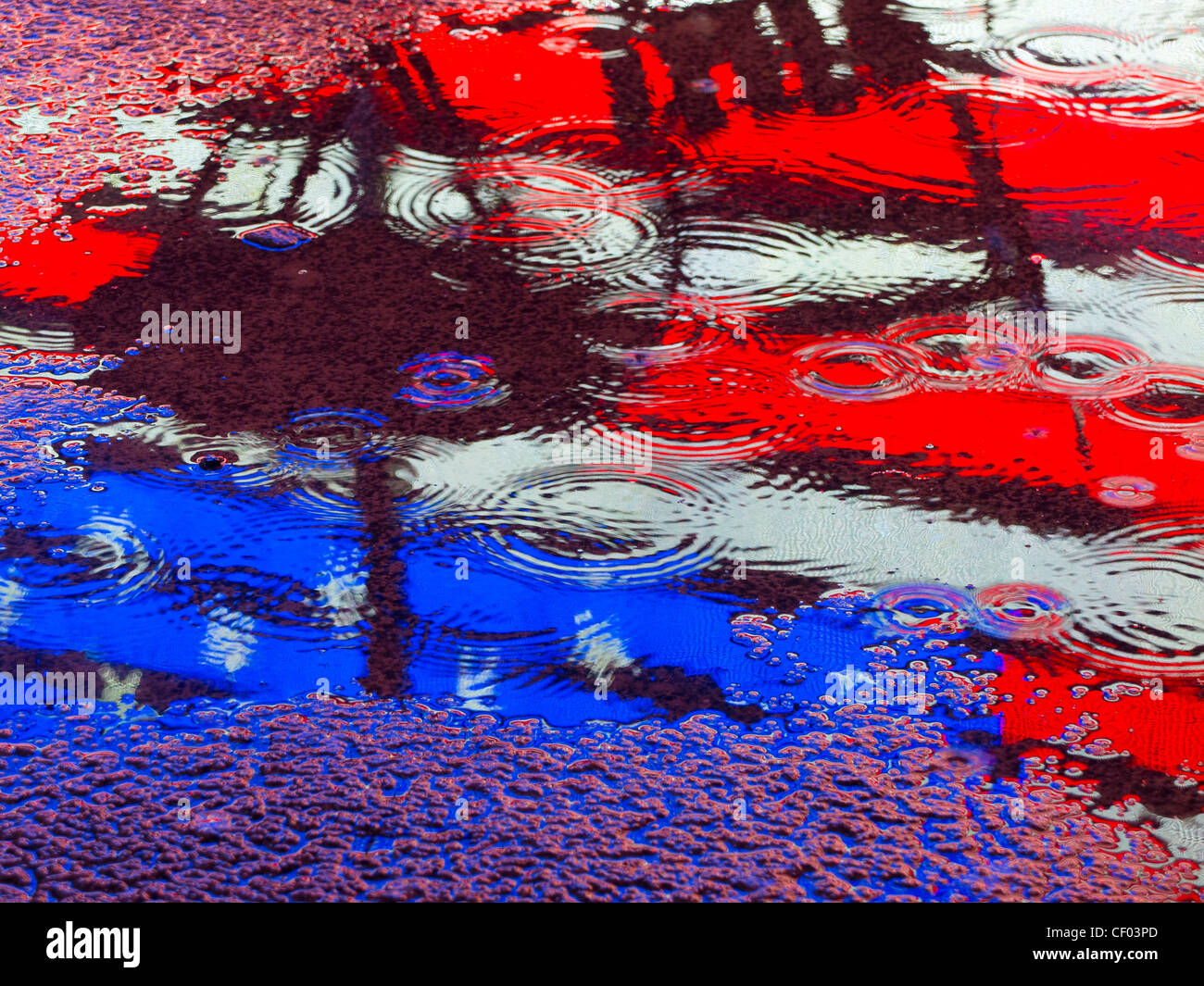 American flag reflection in a puddle - Stock Image