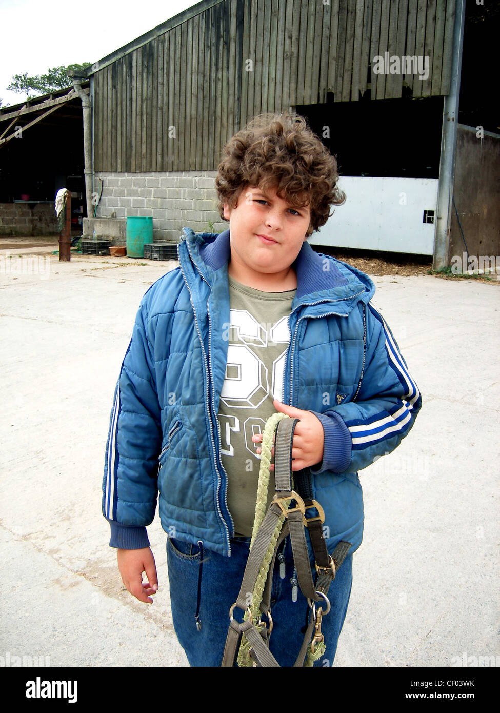 A brown curly haired male, wearing blue jeans, a khaki top and blue quilted jacket, holding a horse's bridle - Stock Image