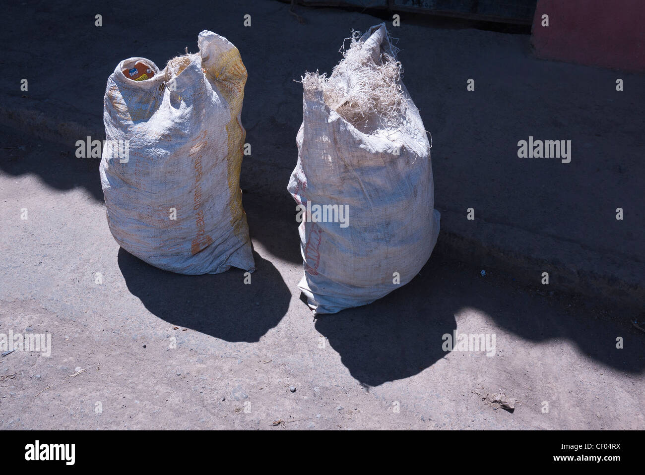 Two stuffed sacks of grain sit on the asphalt half in sun half in shadow in a village in Ecuador. - Stock Image