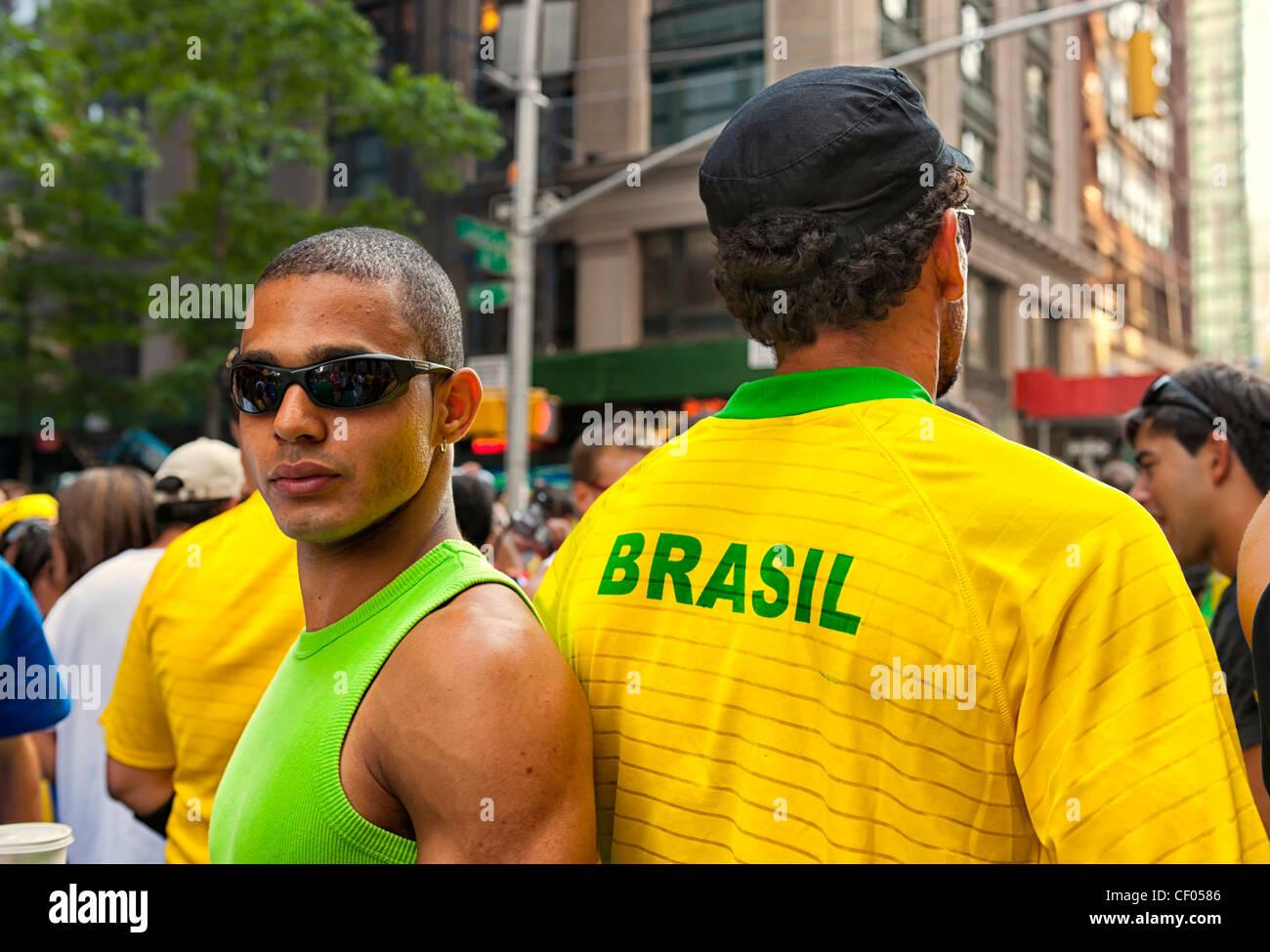 At Brazilian Day Festival, 2 men back to back, 1 in Brasil shirt, Little Brazil, New York City, NY USA, on August - Stock Image
