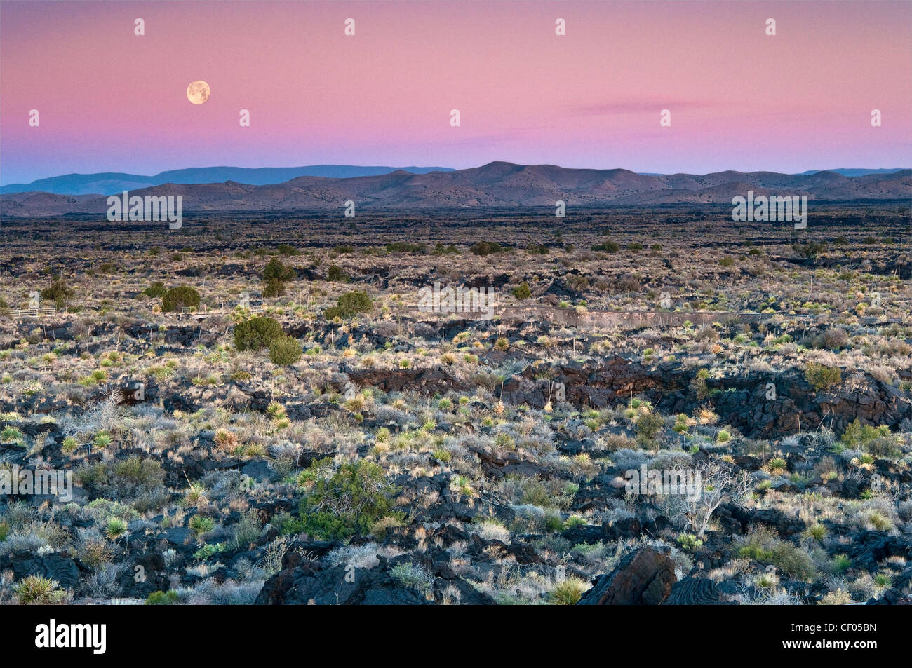 Moon setting down at sunrise over Carrizozo Malpais lava field, Valley of Fires, near Carrizozo, New Mexico, USA - Stock Image