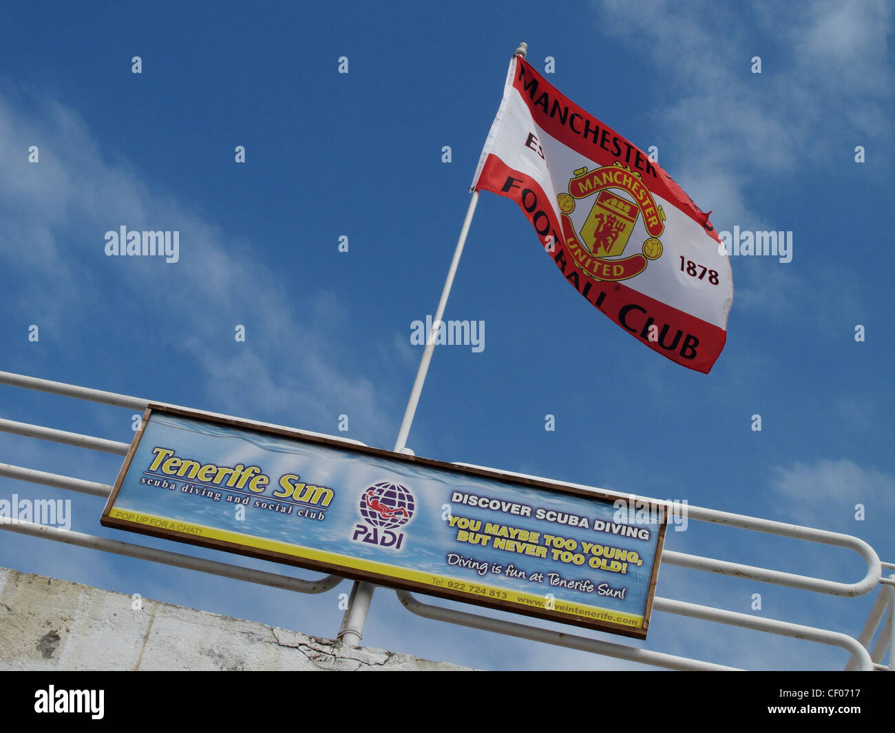 A Manchester United supporters flag flies from a railing above a beach near Playa de Las Americas, Tenerife, Canary - Stock Image