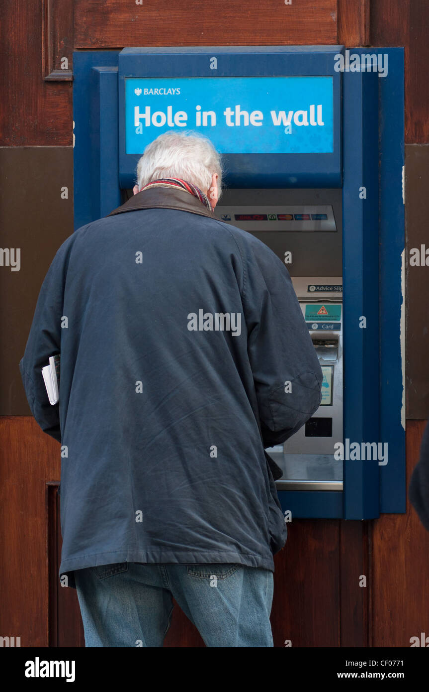 """People using local cash Barclays """"Hole in the Wall"""" cash machine, England, UK. Stock Photo"""
