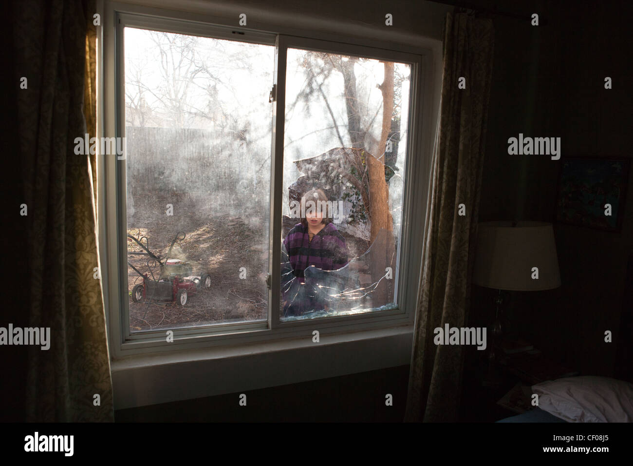 A nine year old boy stares at a broken window. - Stock Image