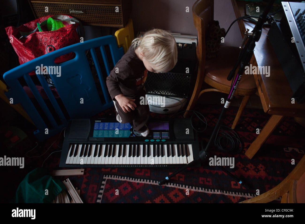 One year old boy stepping on his parents' musical equipment, keyboard and drum machine. - Stock Image