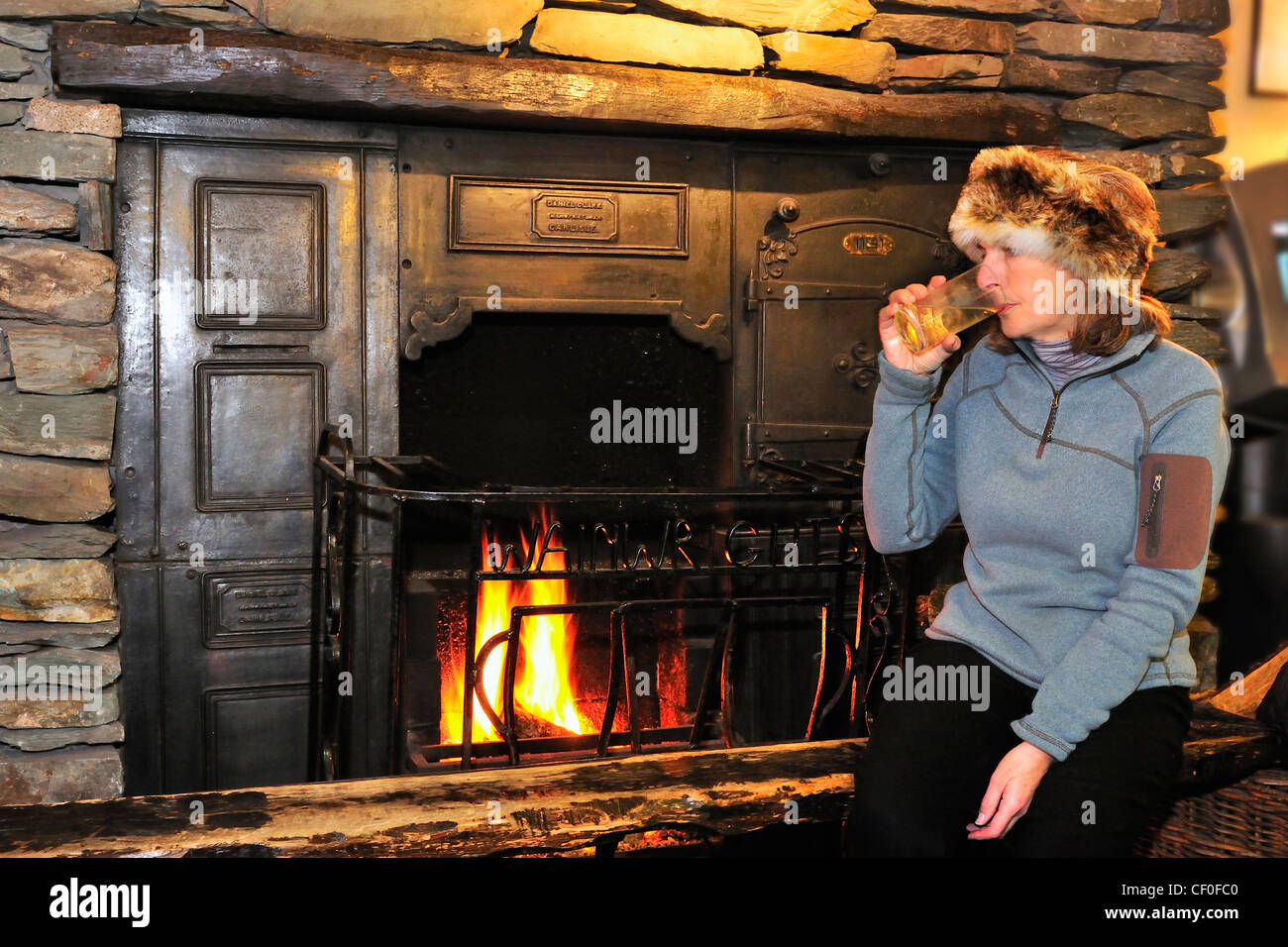 Lady walker   sitting on a fire side seat drinking a half pint of Langdale 's ale at Wainwrights  Inn Elterwater - Stock Image