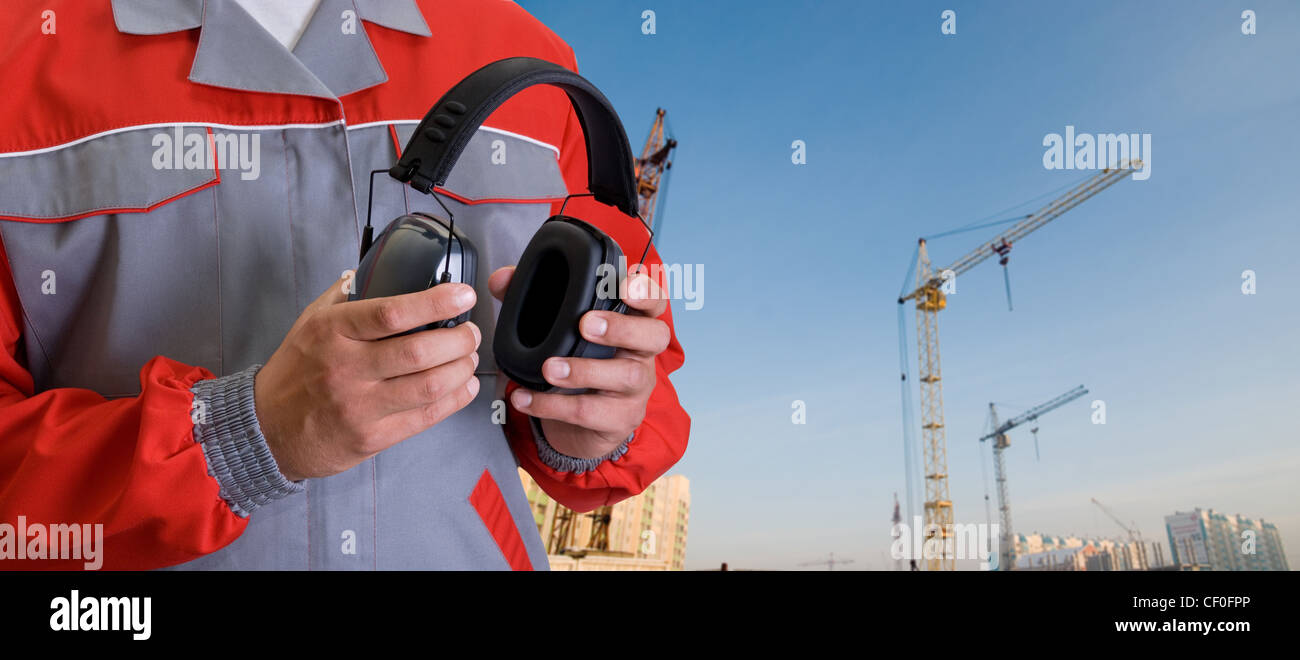 protective headphone at man hands on building background Stock Photo