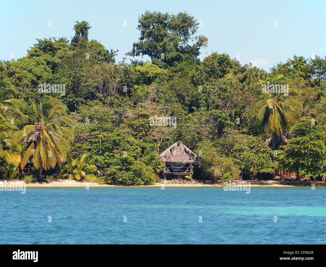 Landscape of tropical island beach with an open-air hut - Stock Image