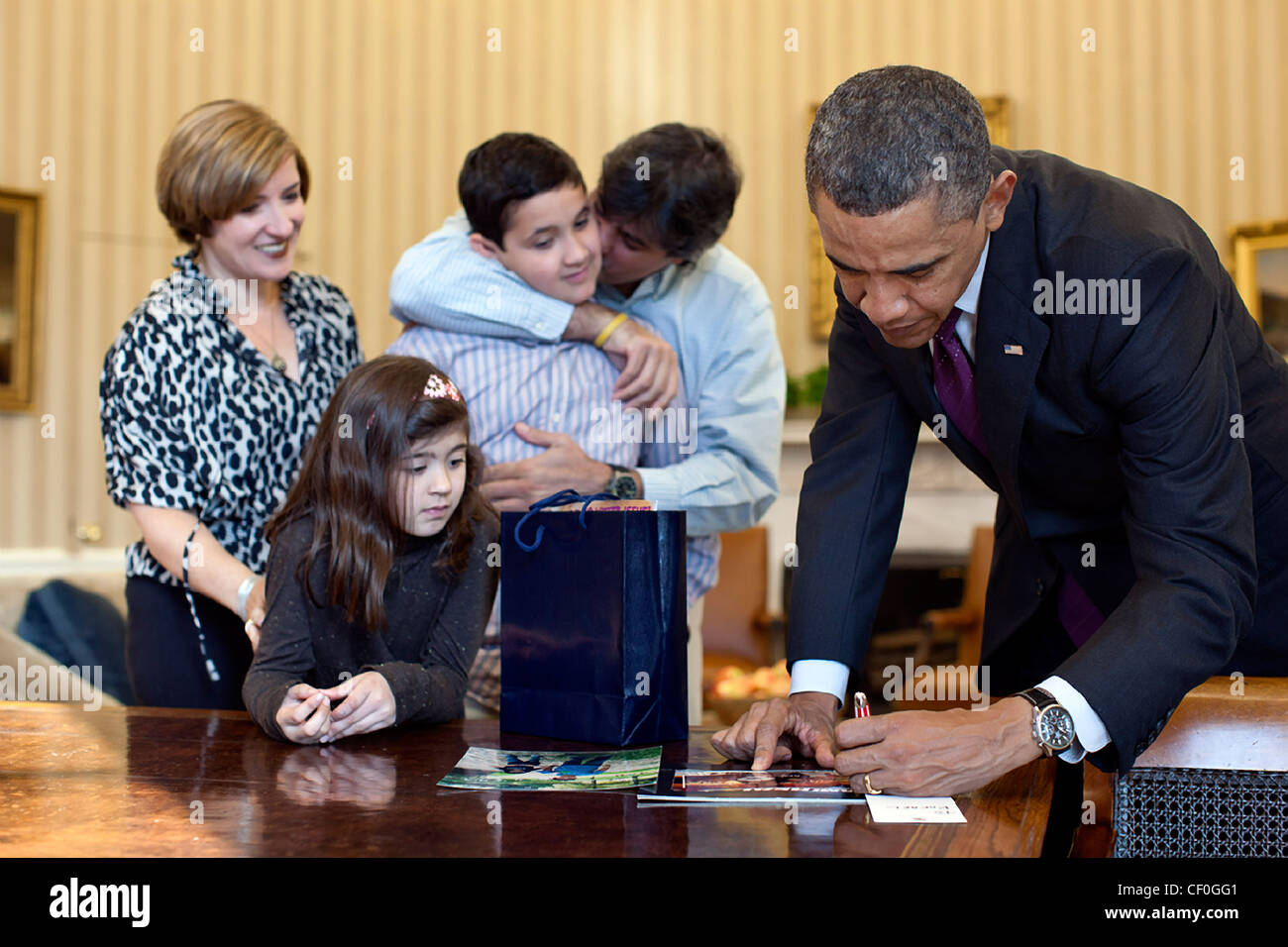 President Barack Obama signs items for Make-A-Wish child Rafael Mullet during a visit in the Oval Office January - Stock Image