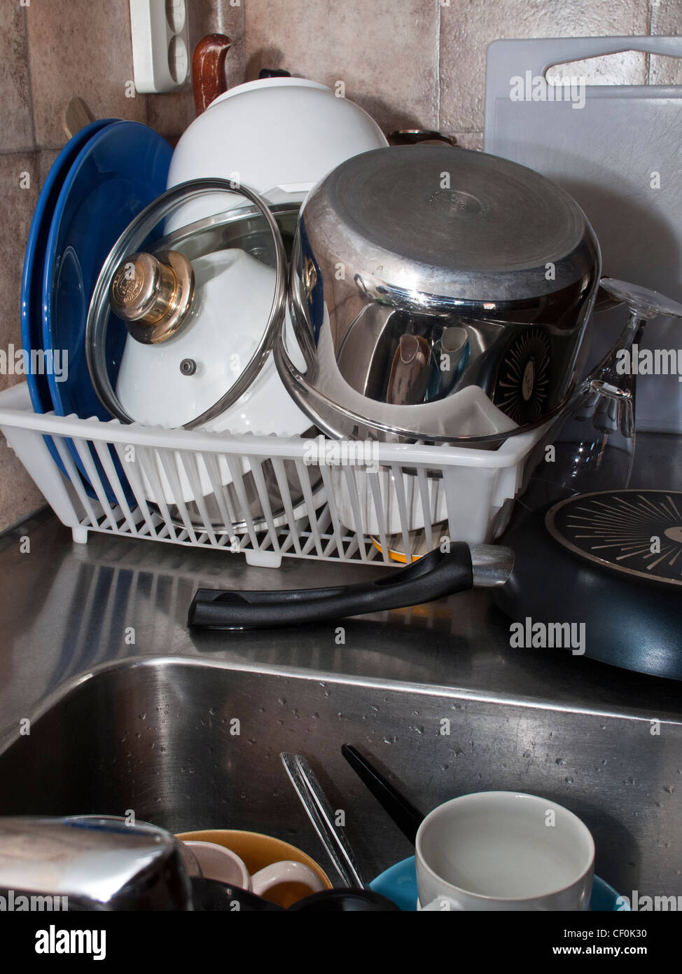 Plastic kitchen drain dish rack full with untidy dishes and utensils. Messy - Stock Image