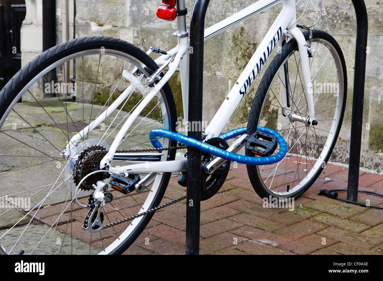 Expensive bicycle secured to a metal post with heavy duty chain and lock - Stock Image