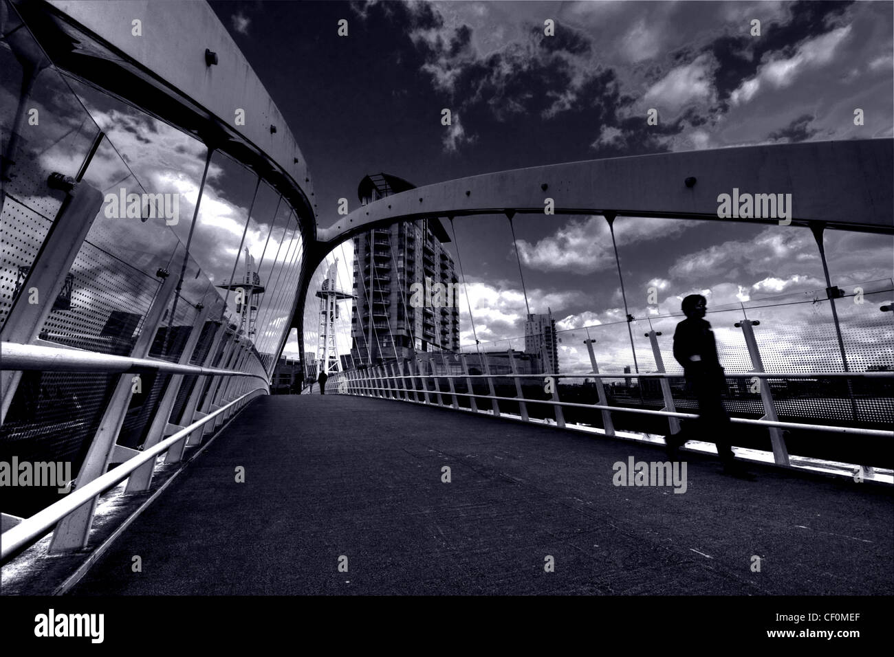 Runner crossing The Salford Quays Lifting Bridge, Media City UK, Manchester England - Stock Image