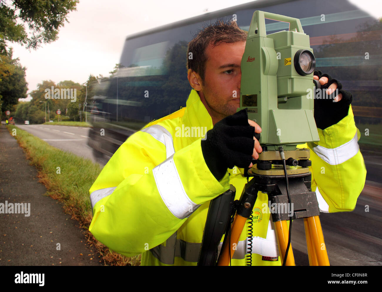 CWAC local authority surveyor on A556 Northwich bypass looking towards Chester with Leica survey instrument. Lorry - Stock Image