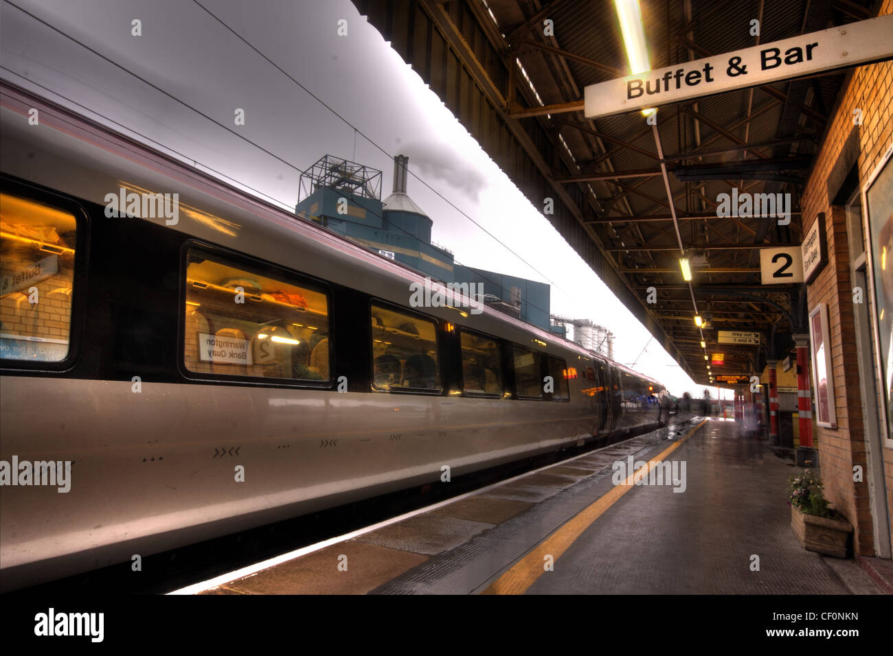 A Virgin train arriving at Bank Quay west coast mainline Railway Station, Warrington, Cheshire, UK at dusk - Stock Image
