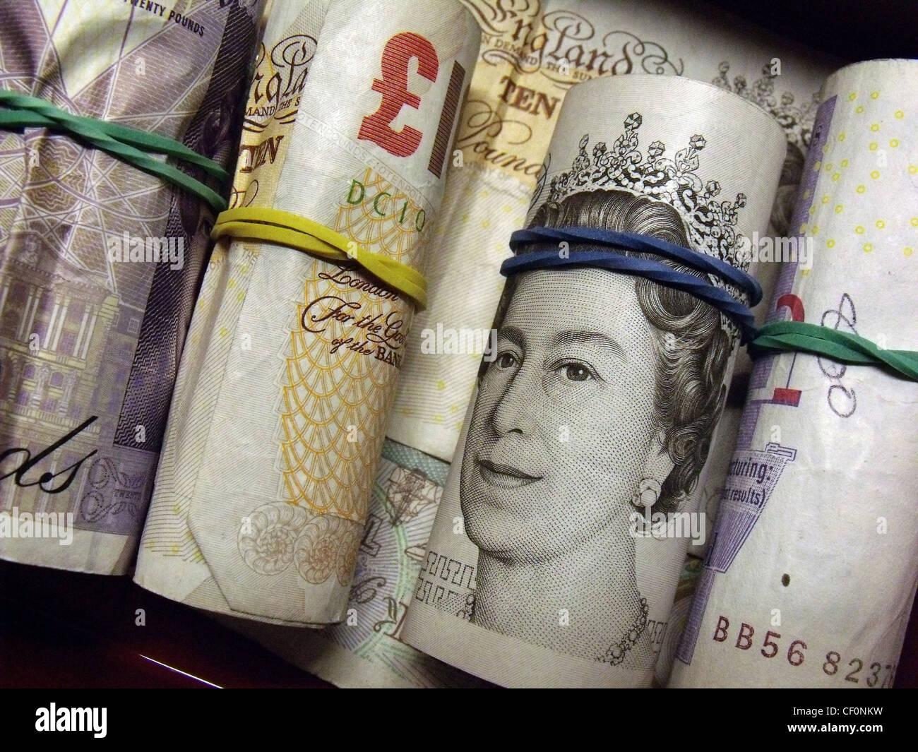 Tuesdays takings, rolls of ten and twenty pound notes with elasticbands - Stock Image