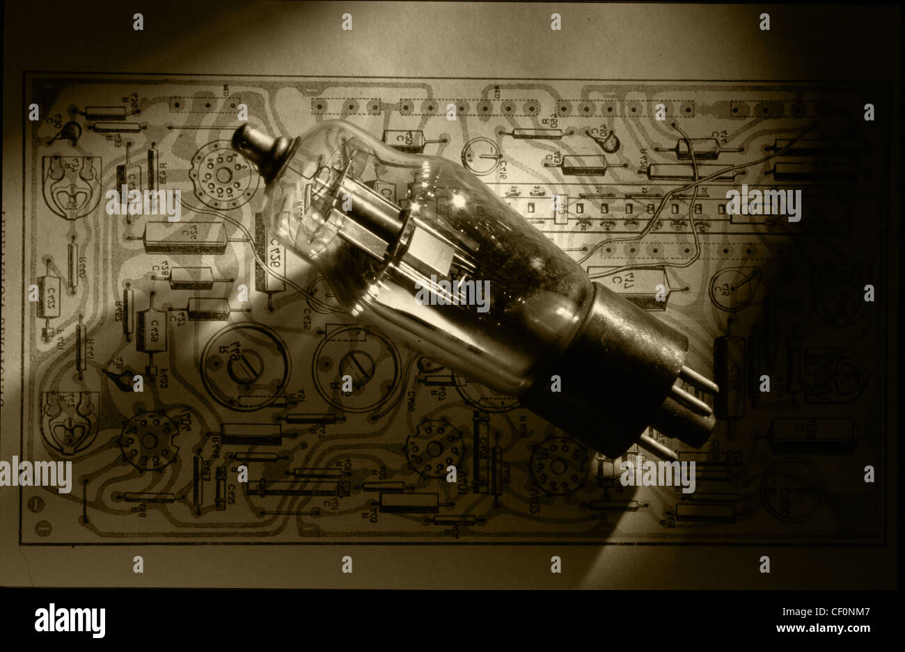 Old style Mullard triode valve sitting on a printed circuit wiring diagram from 1960 - Stock Image
