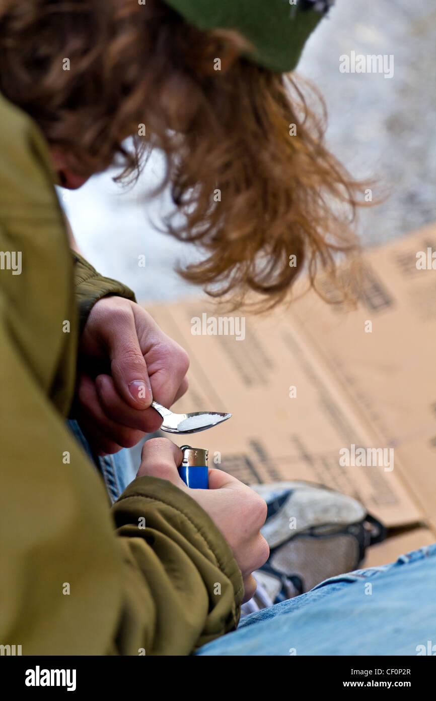 Drug addicted homeless man preparing heroin - Stock Image