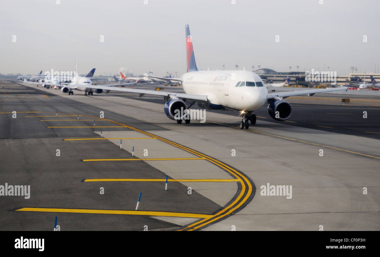 Commercial airliners lined up on runway, awaiting take-off,  at Newark Liberty International Airport, Newark, NJ - Stock Image