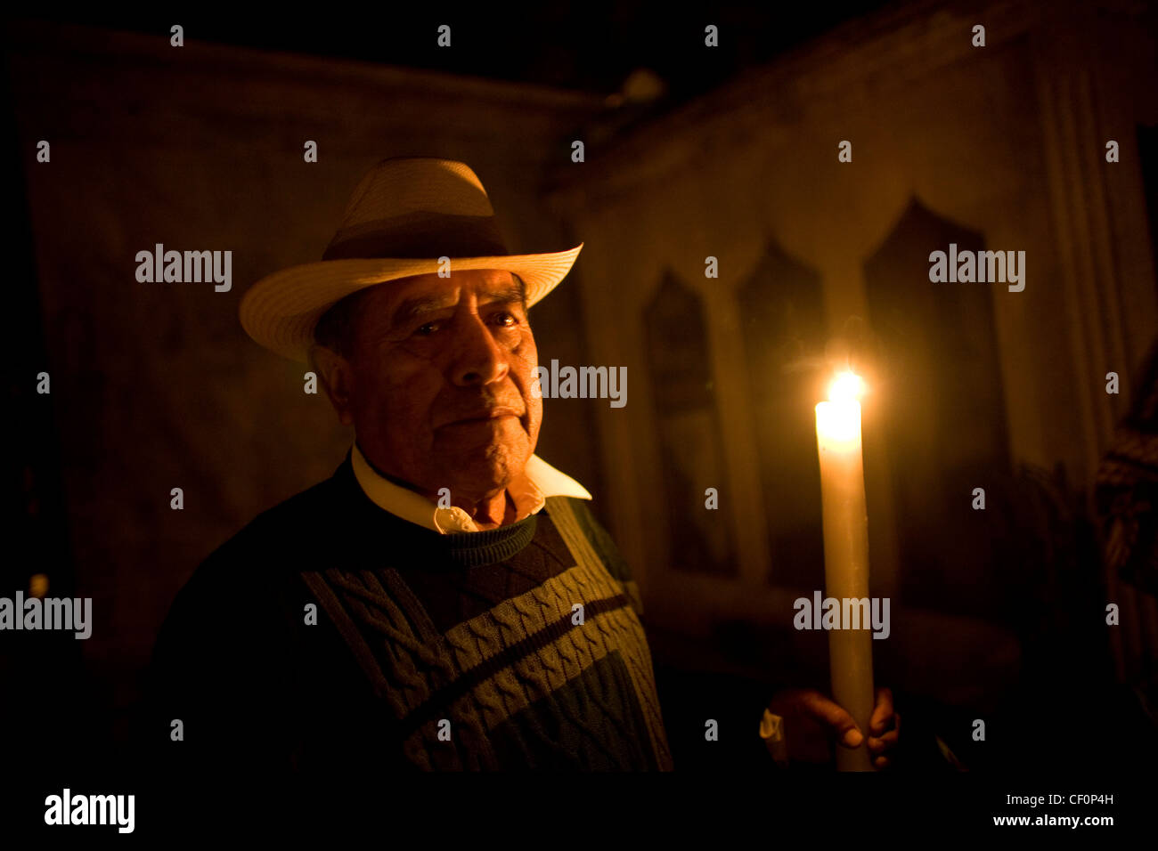 A man holds a candle by the grave of a family member cemetery in San Gregorio Atlapulco on the outskirts of Mexico - Stock Image