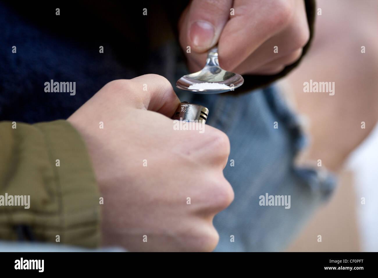 Close up of drug addicted homeless man preparing heroin - Stock Image