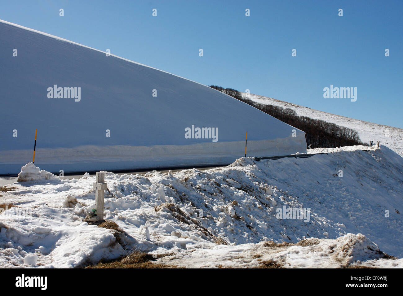 Mountain pass on road to Castelluccio hill town  in Le Marche,Italy after a heavy snow fall,with a clear blue sky. - Stock Image