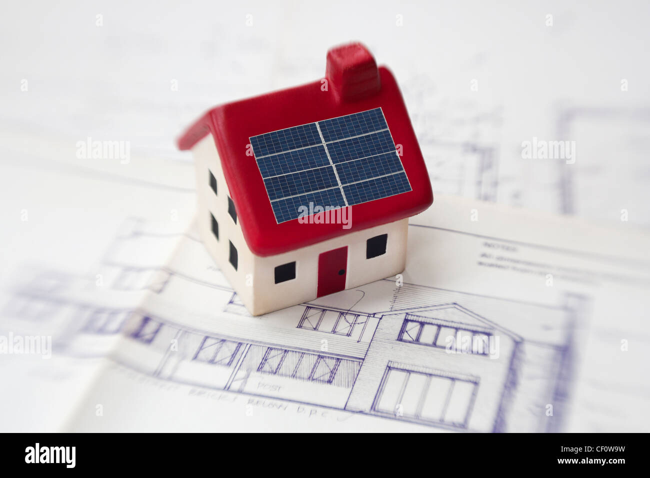 model house with solar panels on architects plans - Stock Image