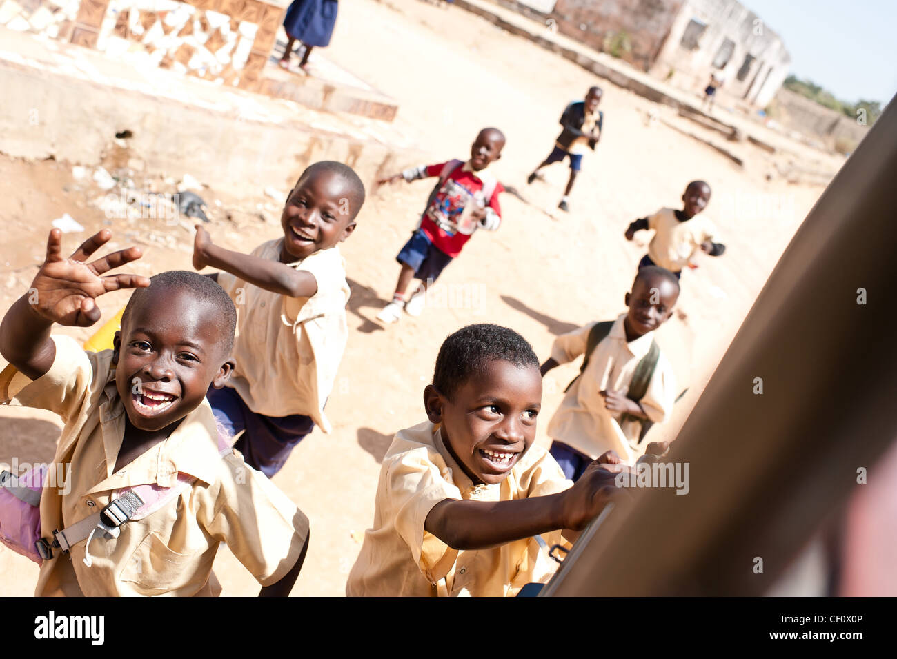 African school children smiling chasing after vehicle - Stock Image
