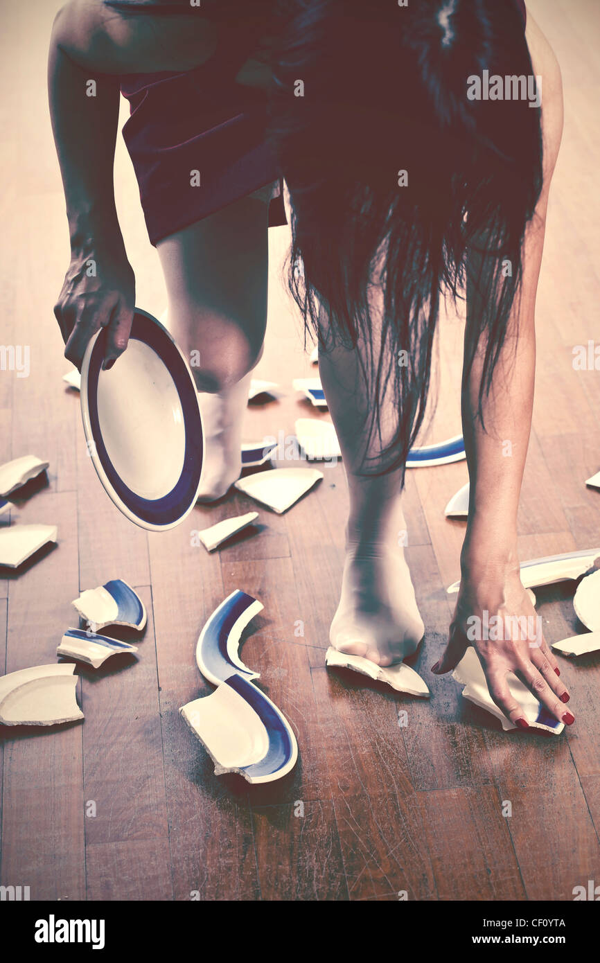 Woman sitting on the floor and picking up pieces - Stock Image