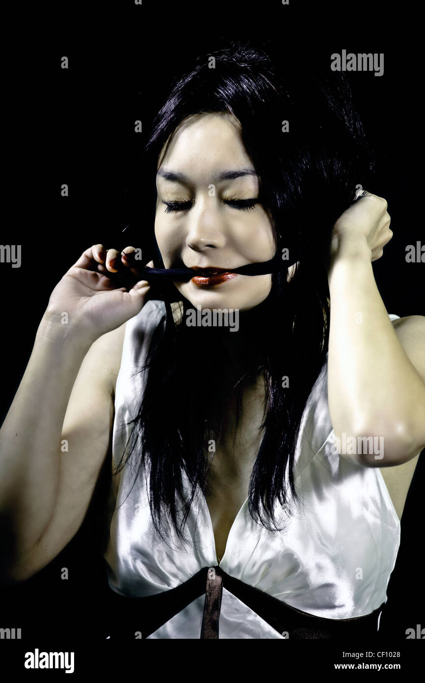 woman tries to get rid of black gag - Stock Image