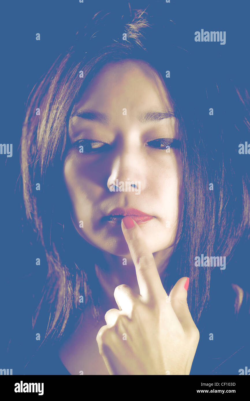pretty Japanese woman holds her finger to her mouth - Stock Image