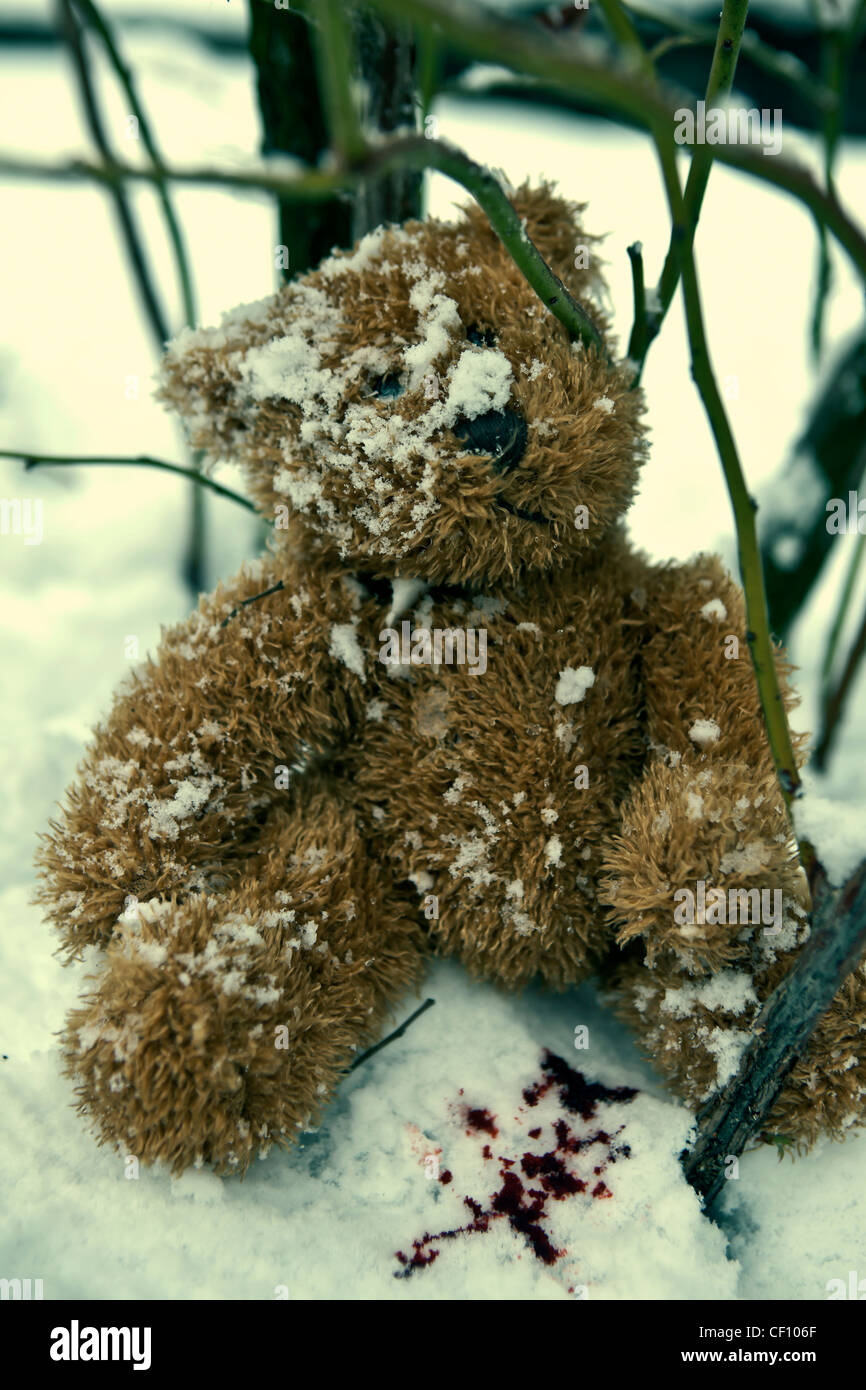 a forgotten teddy bear in the snow with blood drops - Stock Image