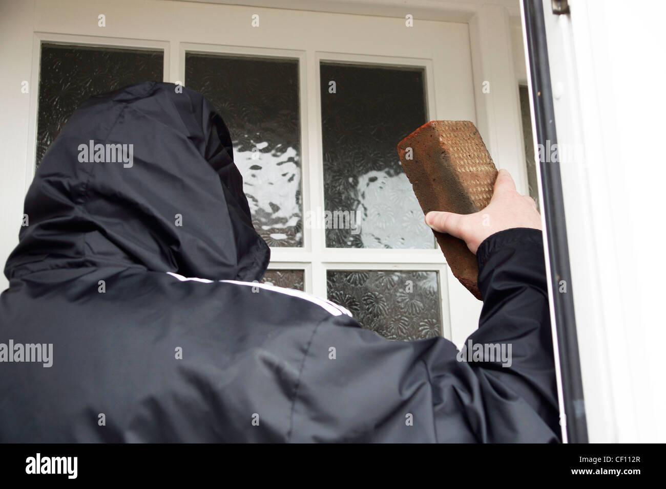 Undesirable character rogue hoodie smashing a brick through a glass window pane MODEL RELEASED Stock Photo