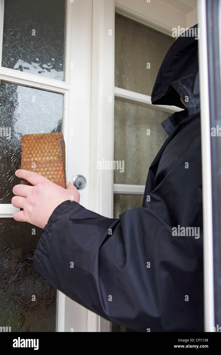Undesirable character rogue hoodie smashing a brick through a glass window pane MODEL RELEASED - Stock Image