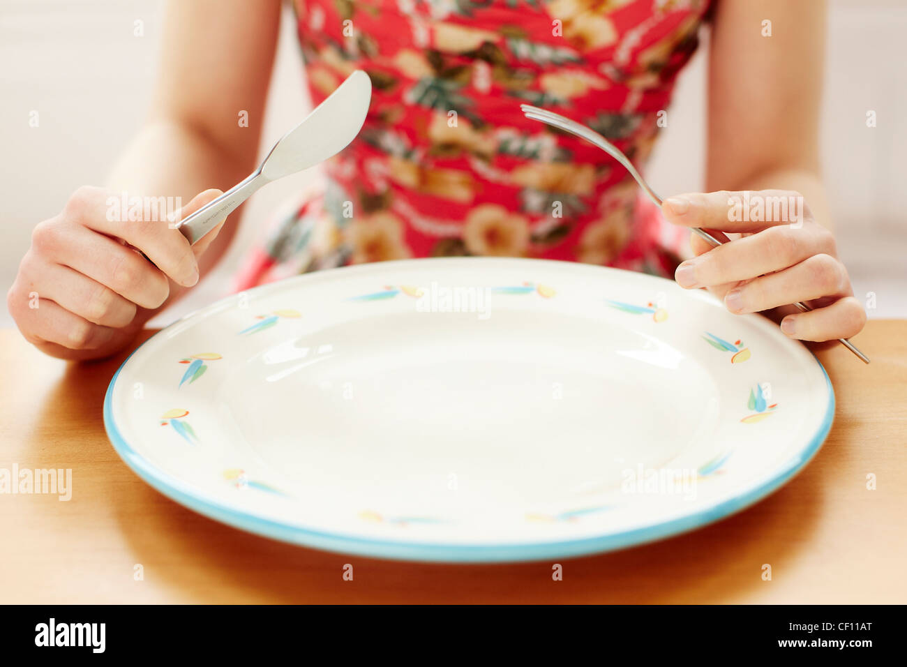 Woman with empty plate - Stock Image