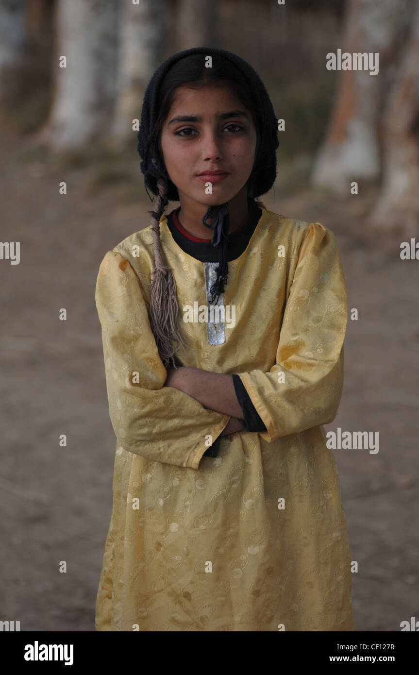 A small girl wearing a black scarf at the fisherman's village, near Fateh Jang, Punjab, Pakistan - Stock Image
