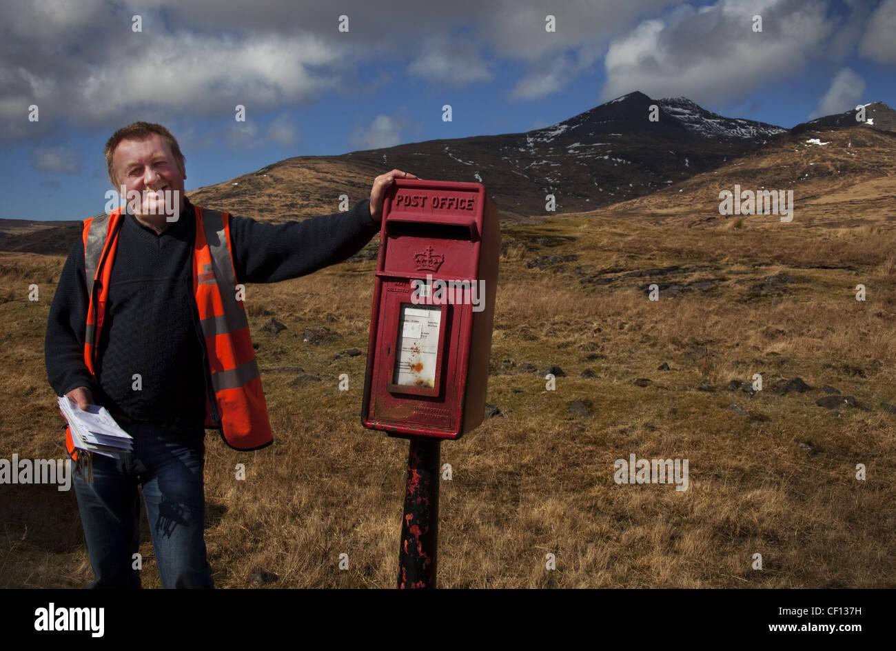 Alastair, Isle Of Mull Postie (postman), western Scotland UK , emptying red post box - Stock Image