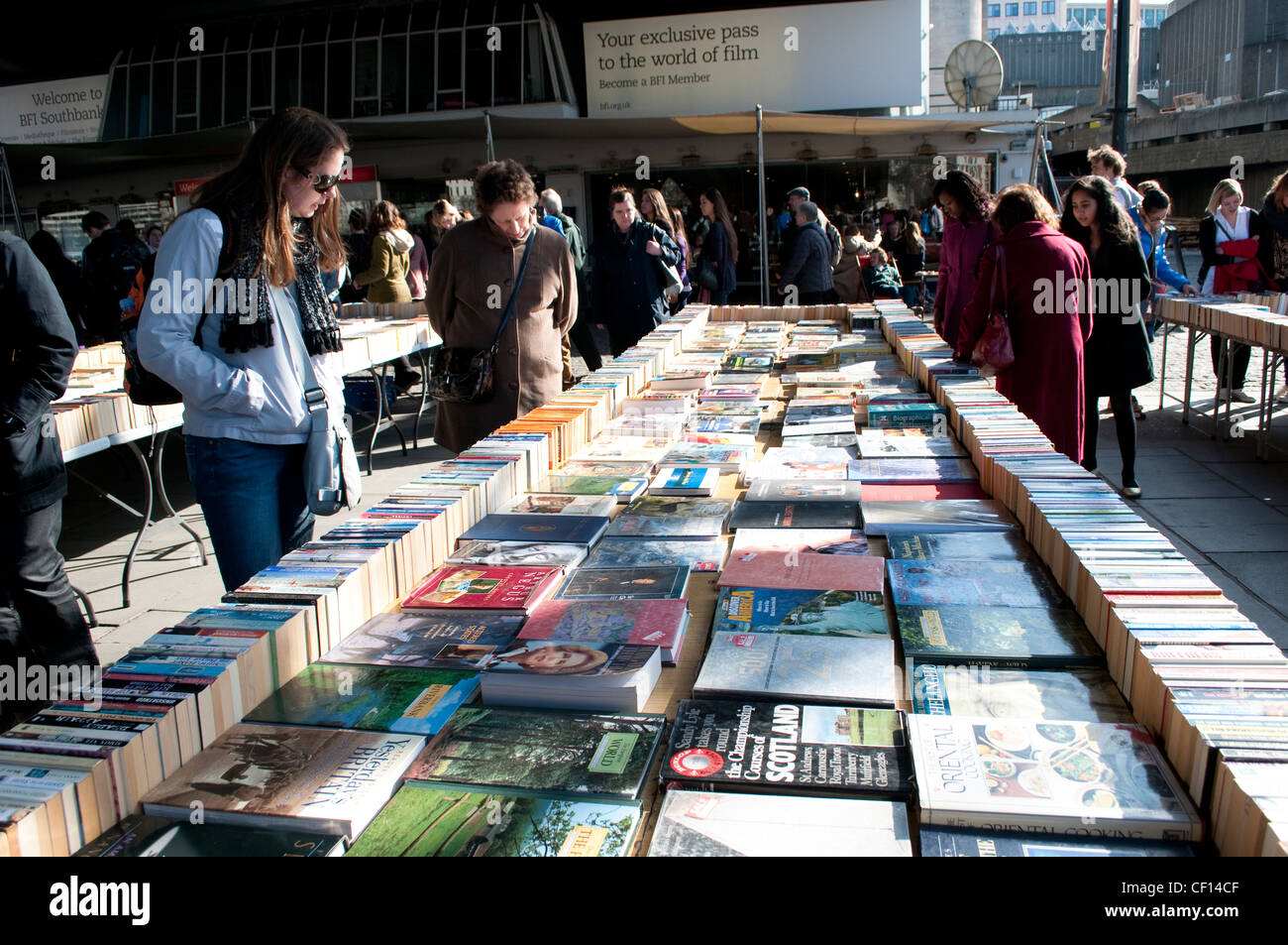People browsing books at second-hand bookstalls under the Waterloo Bridge, , South Bank, London, UK - Stock Image