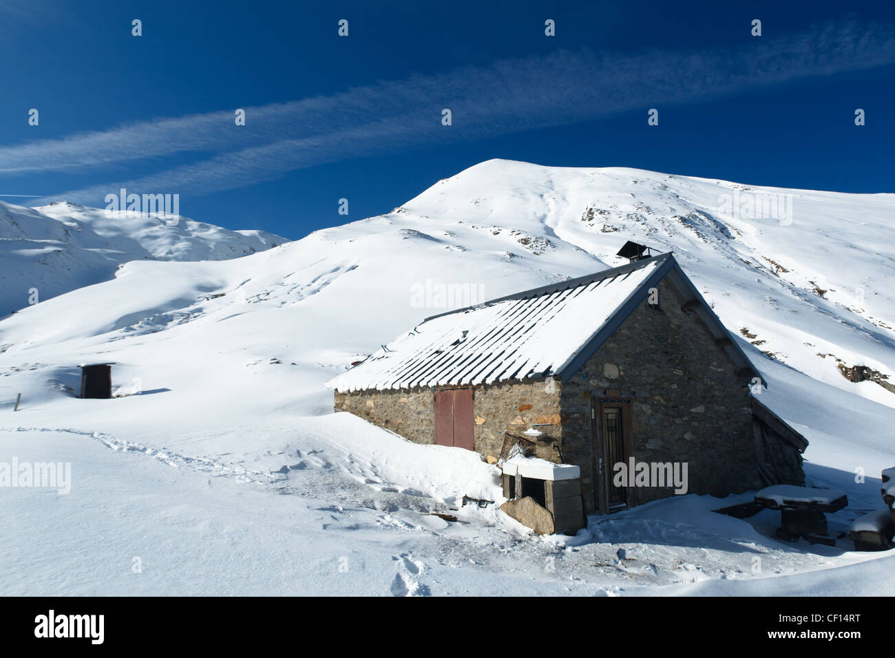 Mountain shelter in snowy mountain landscape near Col de Pause, Ariege, Pyrenees, France. - Stock Image