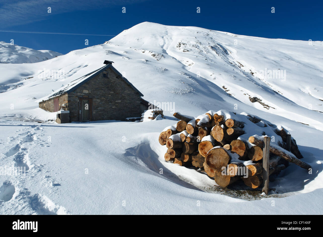 Firewood piled outside a mountain shelter in snowy mountain landscape near Col de Pause, Ariege, Pyrenees, France. - Stock Image