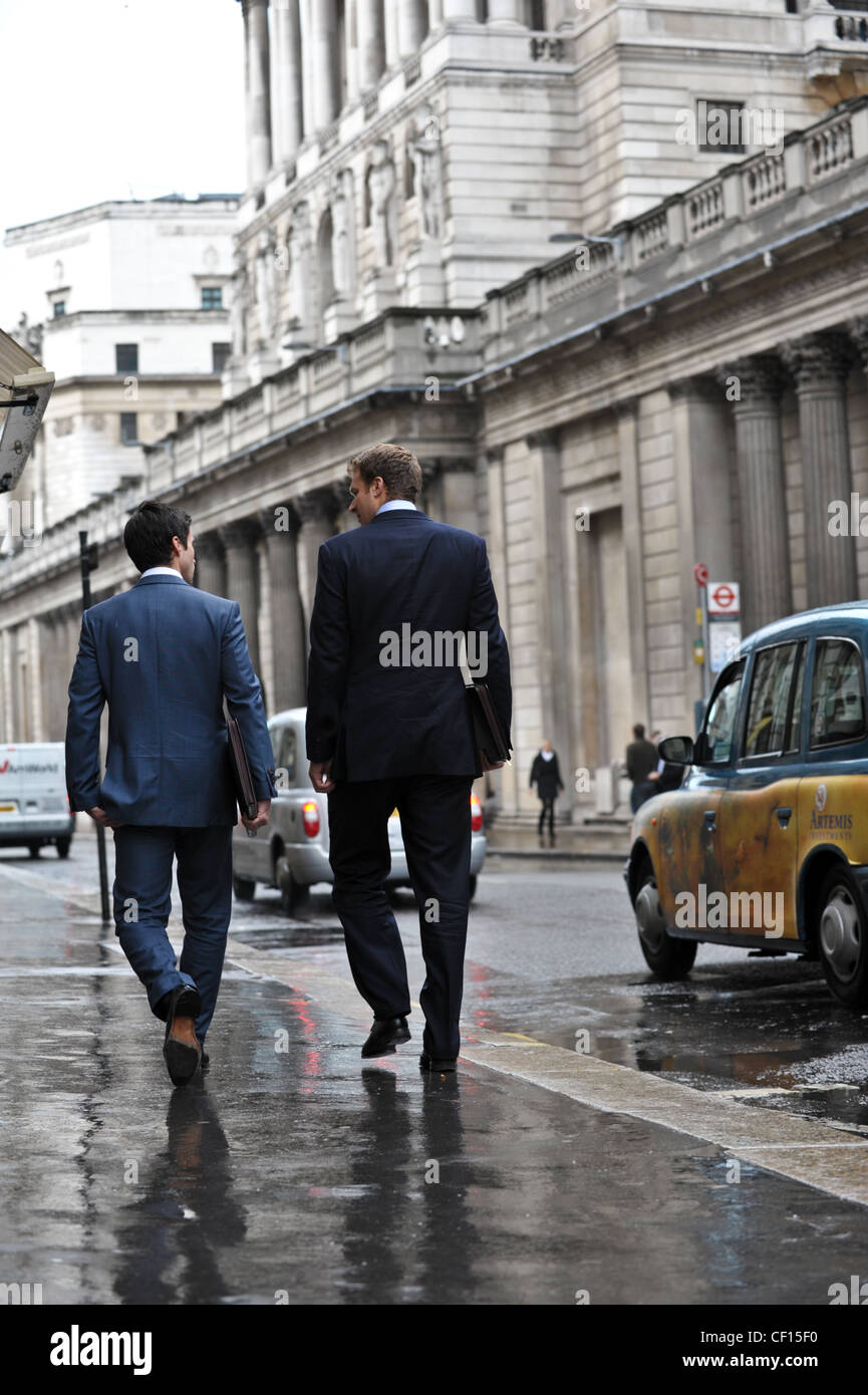 Two City of London bankers chat as they walk past The Bank