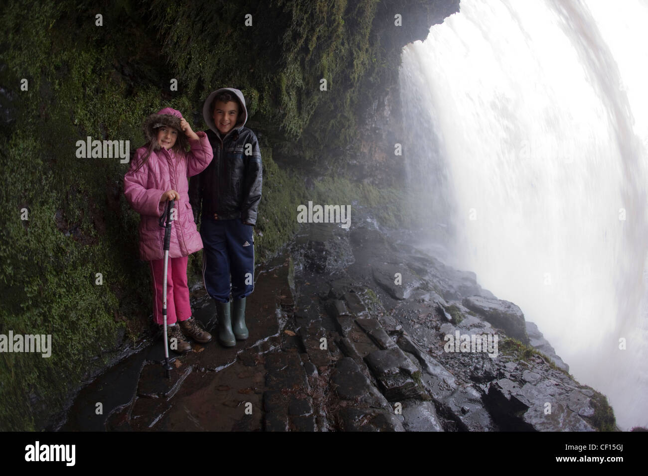 Walking behind the curtain of Scwd yr Eira (or Sgwd yr Eira) waterfall on Afon Hepste in the Brecon Beacons National - Stock Image