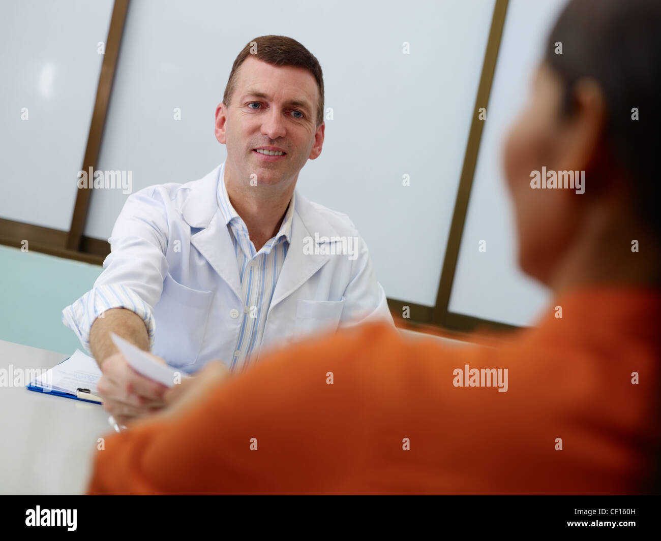 Friendly doctor working and giving assistance to female mature patient in hospital office, writing prescription - Stock Image