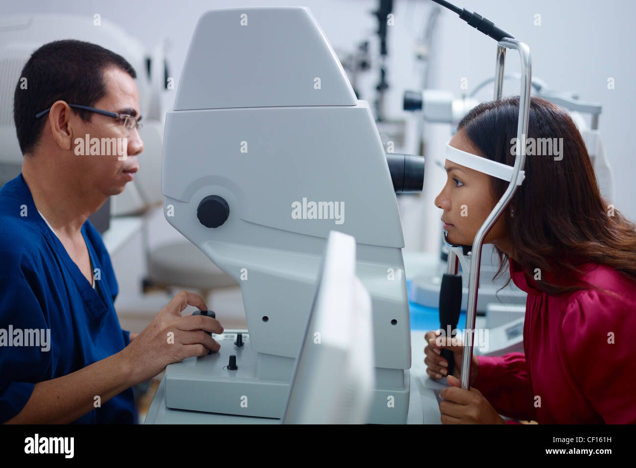 Asian doctor at work during eyesight exam to adult woman in hospital. Side view - Stock Image
