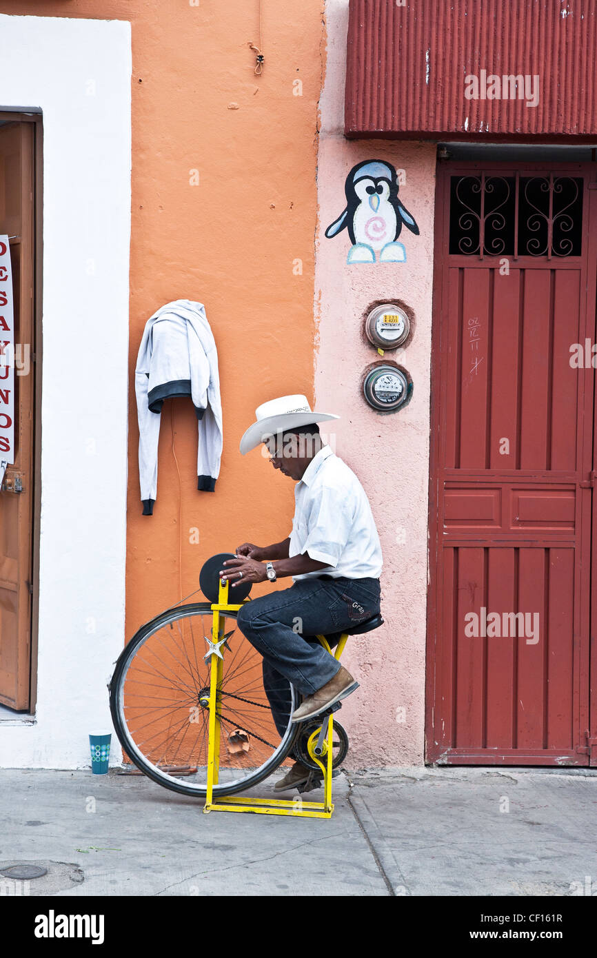 itinerant knife sharpener plying old trade with traditional improvised sharpener tool on a street in Oaxaca de Juarez - Stock Image