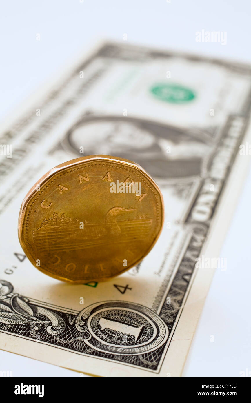 Upright Canadian One Dollar Coin On Top Of A Us One Dollar Bill - Stock Image