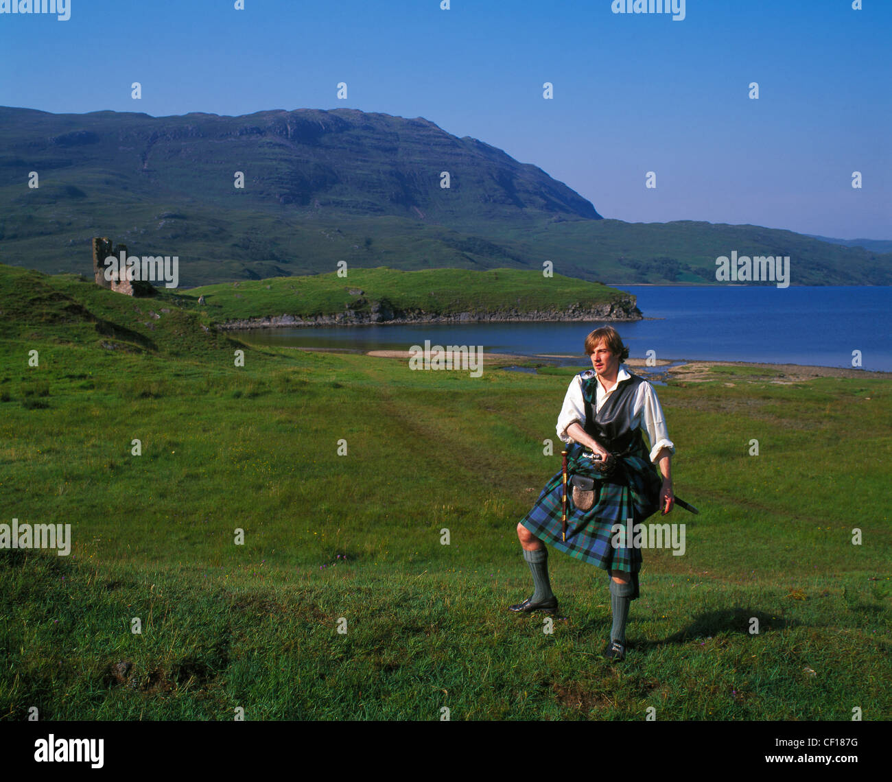 Highlander in Glen Assynt with the ruin of Ardvreck Castle in background, Highland Region, Scotland, UK. - Stock Image