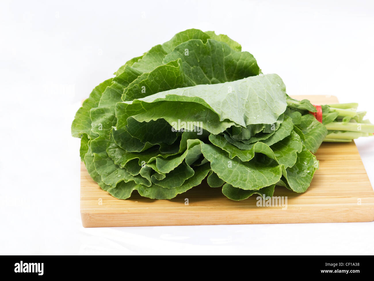 Collard greens on a wooden cutting board on white background - Stock Image