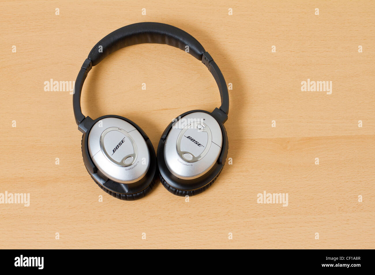 Noise canceling headphones Bose on a wooden background - Stock Image