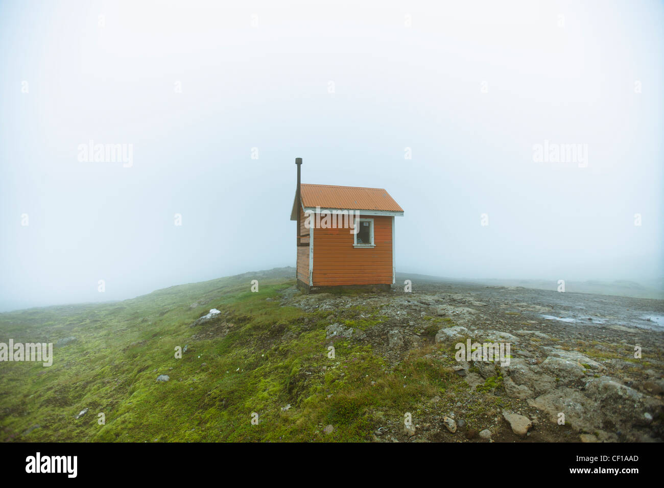 A Small Structure In The Middle Of A Wide Open Space Surrounded By Fog; Iceland - Stock Image