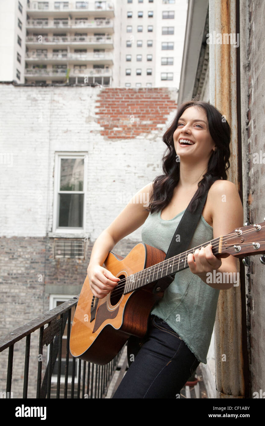 Woman playing guitar on fire escape Stock Photo